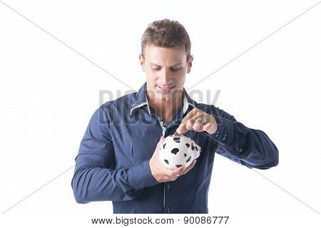 Young man putting coin in piggy-bank, isolated