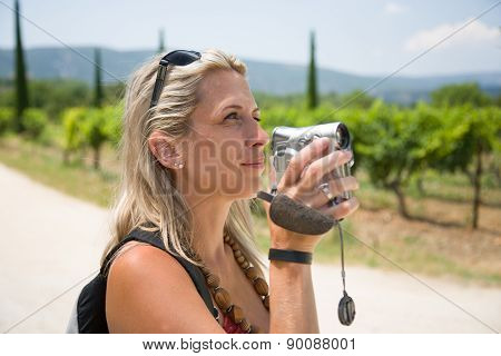 Pretty blonde woman with camcorder in provence