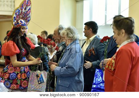 ST. PETERSBURG, RUSSIA - MAY 6, 2015: Girl giving flowers and gifts to WWII veterans during opening ceremony of International freestyle wrestling tournament Victory Day in Mikhailovsky manege