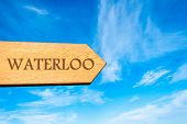 Wooden arrow sign pointing destination WATERLOO BELGIUM against clear blue sky with copy space available. Travel destination conceptual image poster