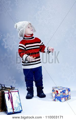 Happy Small Boy In Knitted Hat And Pullover With Gift Boxes