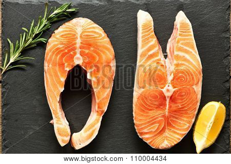 Raw salmon steaks and ingredients on slate background