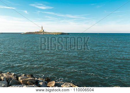 Monumental lighthouse on small island surrounded by blue sea