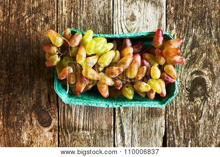 Fresh grapes on old wooden background
