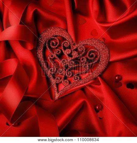 Valentine red heart on red silk background. Valentine's Day