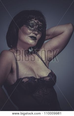 sensual and seductive brunette woman in black lingerie and mask
