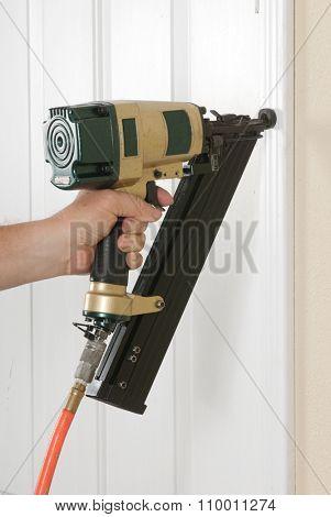 Carpenter using an angle nail gun to finish door trim