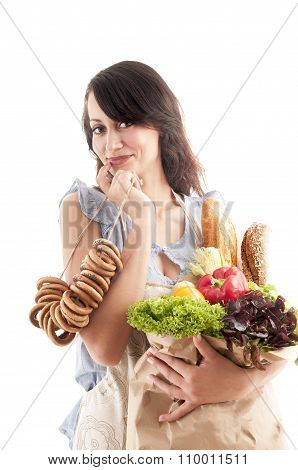 Pretty Woman  Holding A Grocery Bag Full Of Bread And Vegetables.