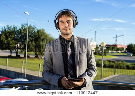 Businessman Using A Tablet And Headphones While Smiling