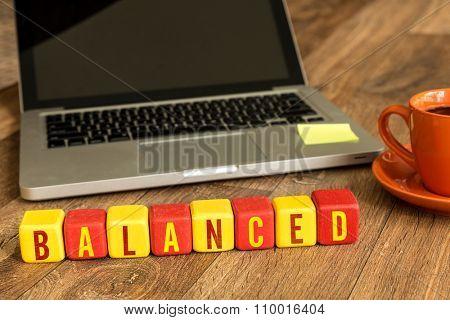 Balanced written on a wooden cube in a office desk