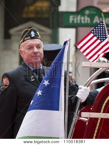NEW YORK - NOV 25 2015: An NYFD and U.S. vet stands on the back of a fire truck along the parade route during the annual Americas Parade up 5th Avenue on Veterans Day in Manhattan.