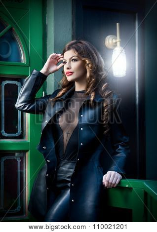 Charming brunette in black leather outfit with green painted door on background. Sexy gorgeous woman