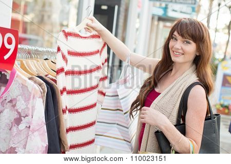 Smiling young woman shopping - looking at clothes with shopping bags