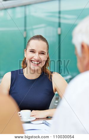 Smiling young woman drinking a cup of coffee in a caf�©