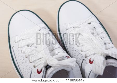 Fashion Ideas And Concepts. Fashionable Stylish White Plimsolls On Wooden Surface.