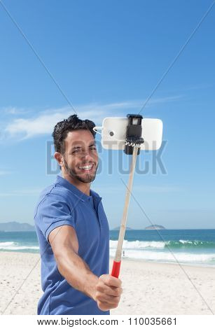 Happy Guy With Blue Shirt And Beard At Beach Taking Selfie With Stick