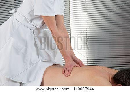 Man Having Shiatsu Massage On His Back By Therapist