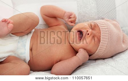 Beautiful baby in diaper with wool cap crying