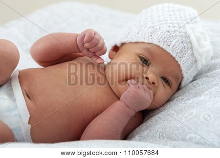 Beautiful baby with wool cap sucking her hand