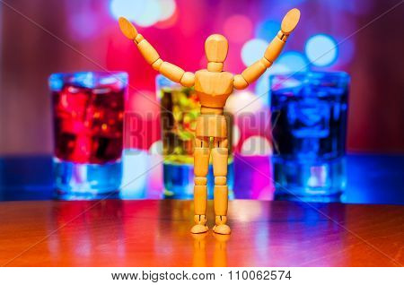 Happy wooden dummy, mannequin or man figurine, silhouette stand against the backdrop of alcohol drin