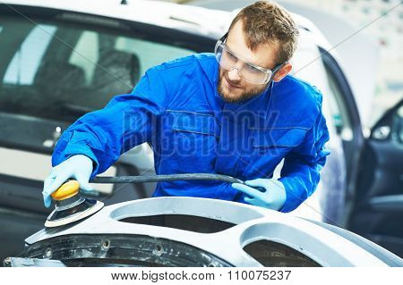 auto mechanic worker  polishing bumper car at automobile repair and renew service station  by power polisher machine