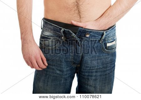 Young shirtless man holding his crotch because of pain.