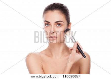 Portrait of woman with makeup brush near her face