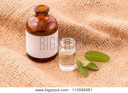 Natural Spa Ingredients Sage Essential Oil For Aromatherapy On Hemp Sacks Background.
