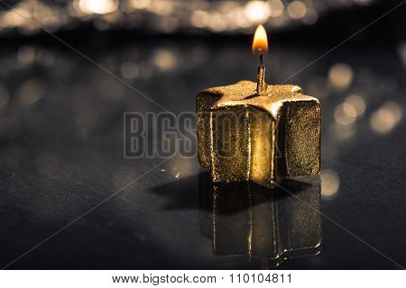 Lit Golden Candle With Reflection And Bokeh Background