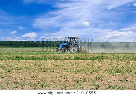 Tractor Working In The Field, Against The Blue Sky