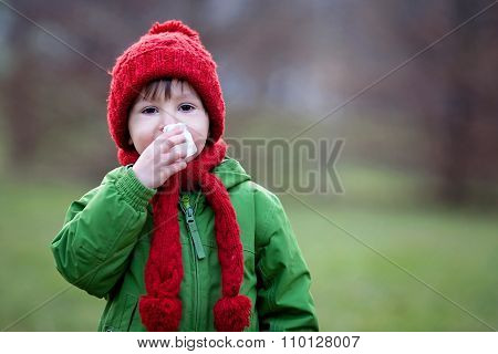 Little Boy, Sneezing And Blowing His Nose On A Sunny Winter Day