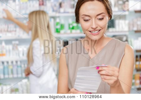 Beautiful girl pharmacist helping a customer