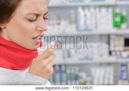 Young woman in drugstore with handkerchief