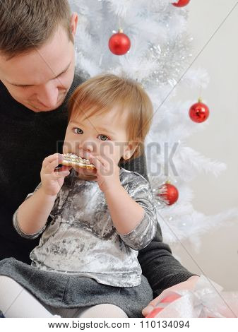 Cute Little Baby Girl Eating Cookies On Father's Knees