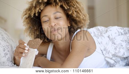 Cute young african-american woman eating chocolate in bed at home