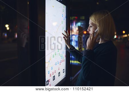 Charming female using city computer for touristic information while talking on mobile phone