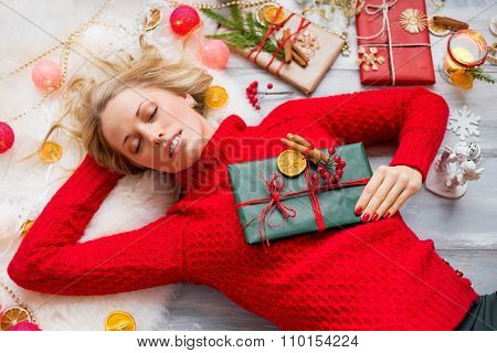 Woman lying on the floor and holding present in hand