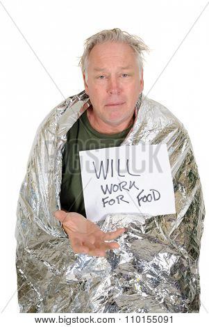 Homeless man wrapped in an emergency survival blanket, holding a piece of paper in front of him with