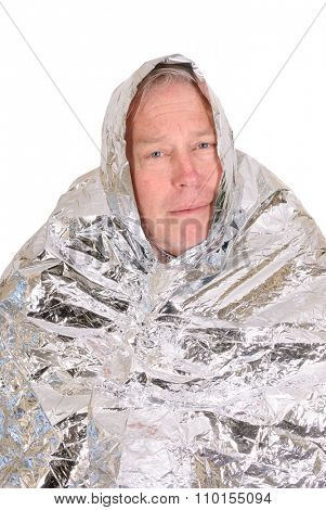 Lost hiker wrapped in an emergency survival blanket isolated on white