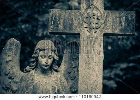 Stone angel and cross on an unknown tomb