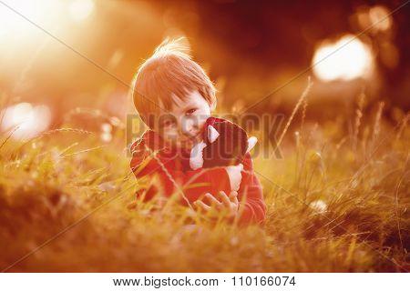 Adorable Boy With His Teddy Friend, Sitting On A Lawn