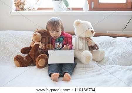 Adorable Cute Baby Boy, Playing On Tablet In Bed, Teddy Bears Around Him