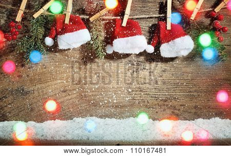 Santa Claus Hats Hanging on Wood Background
