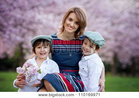 Beautiful Kids And Mom In Spring Park, Flower And Present. Mothers Day Celebration Concept