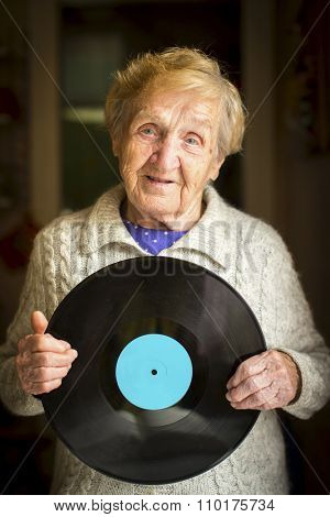 Elderly woman with the vinyl lp record in his hands. Place on vinyl for your text.
