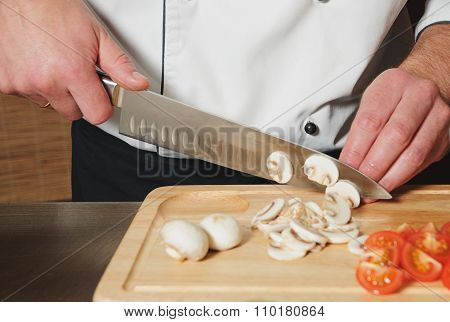 Chef Cutting Mushrooms And Tomats