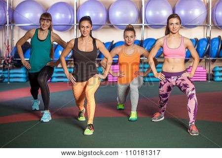 Small group of women doing a leg exercise in aerobics class poster
