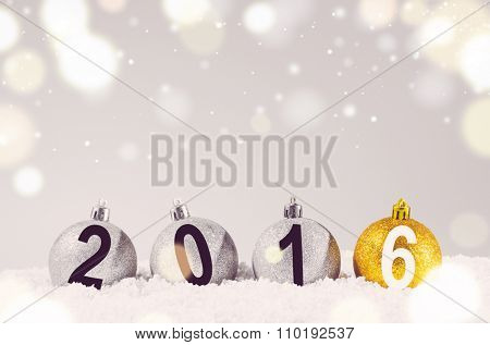 2016 year. Silver and golden decorative christmas balls on snow against grey festive background