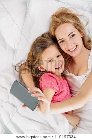 Mother daughter. selfie in white bed