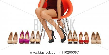 people, fashion, shopping, footwear and style - close up of woman sitting on chair and trying on high heeled shoes
